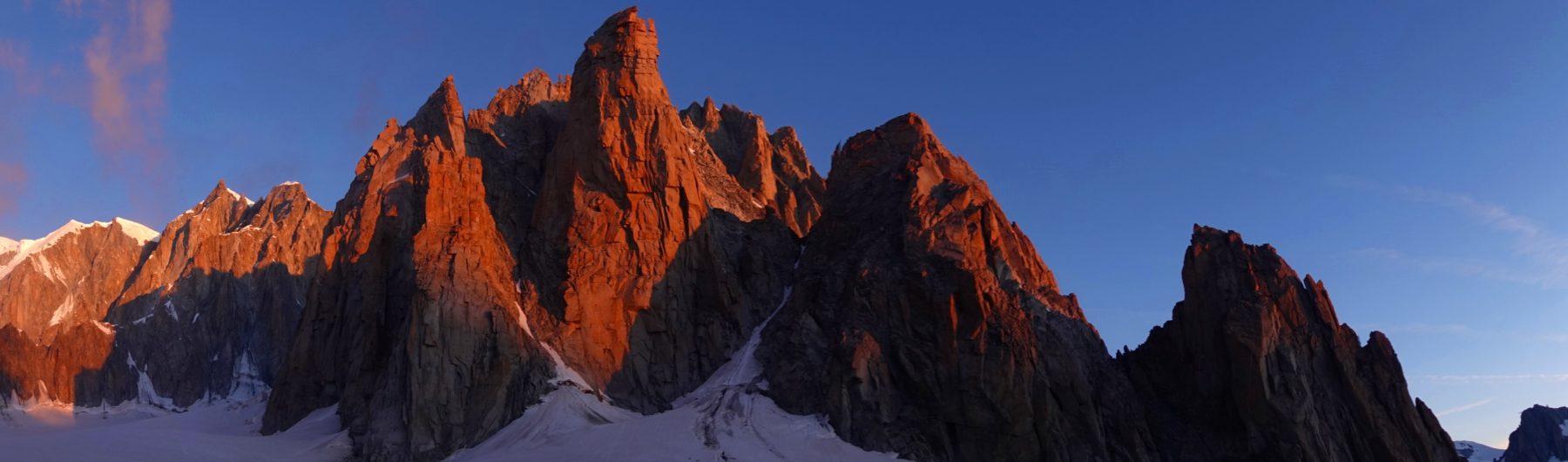 Grand Capucin im Morgenlicht, im Hintergrund der Aufstieg zum Mont Blanc